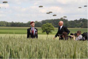 deux hommes dans un champs, présence de photographe et parachutiste en arrière-plan - commémoration du D-Day / crédit studios numériques