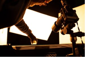 shooting photos d'un flacon en studio – main qui pose le flacon et appareil photos